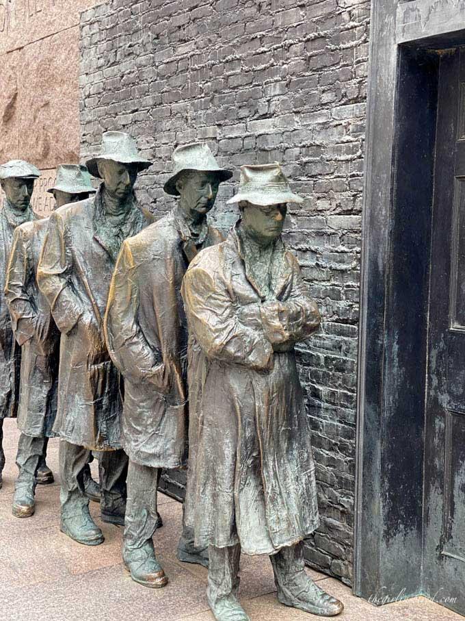 sculptures of men waiting in a bread line with brick background and door