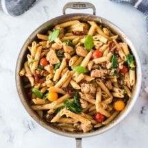 creamy chicken pasta in saucepan with grey dishtowel