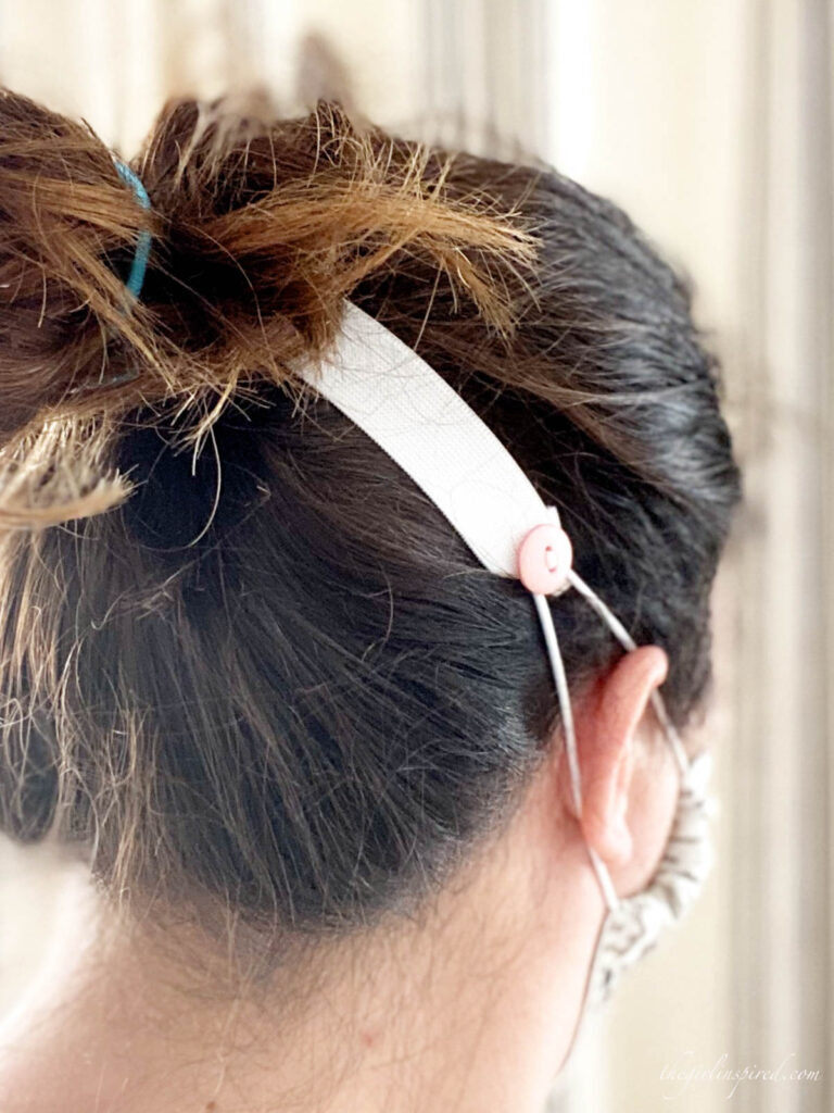 white elastic with pink button across the back of woman's head