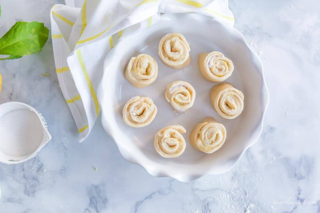 sliced lemon rolls in white pie plate with yellow and white dish towel