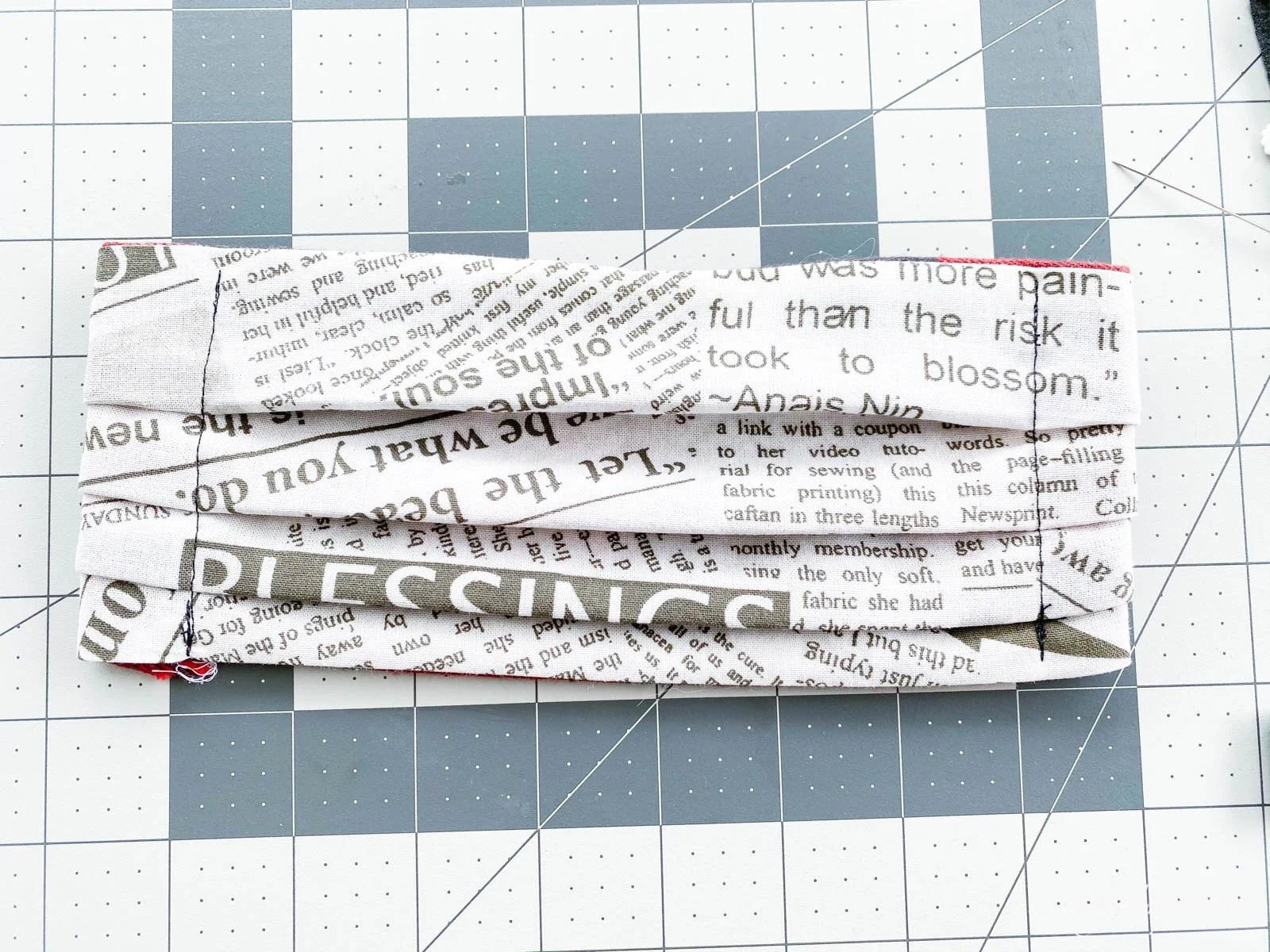 front side of newsprint serger fabric mask on rulered mat