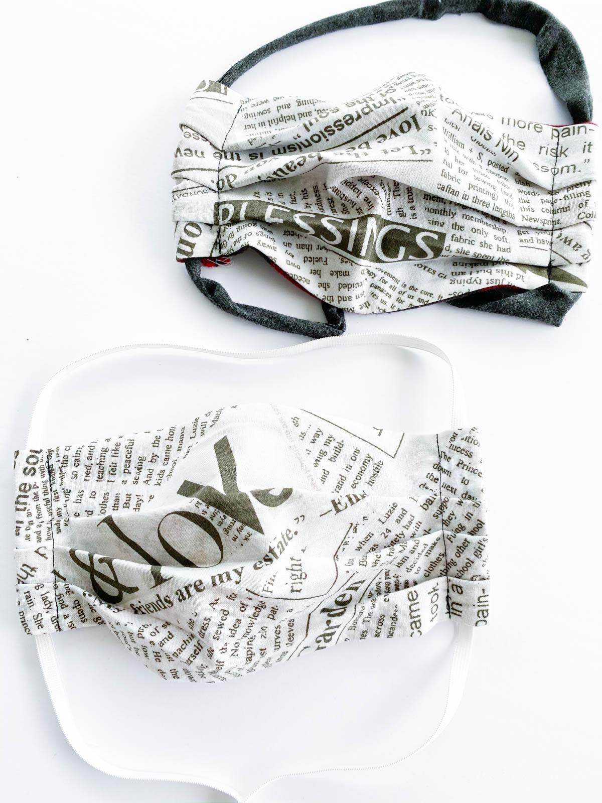 finished serged newsprint fabric masks on white background