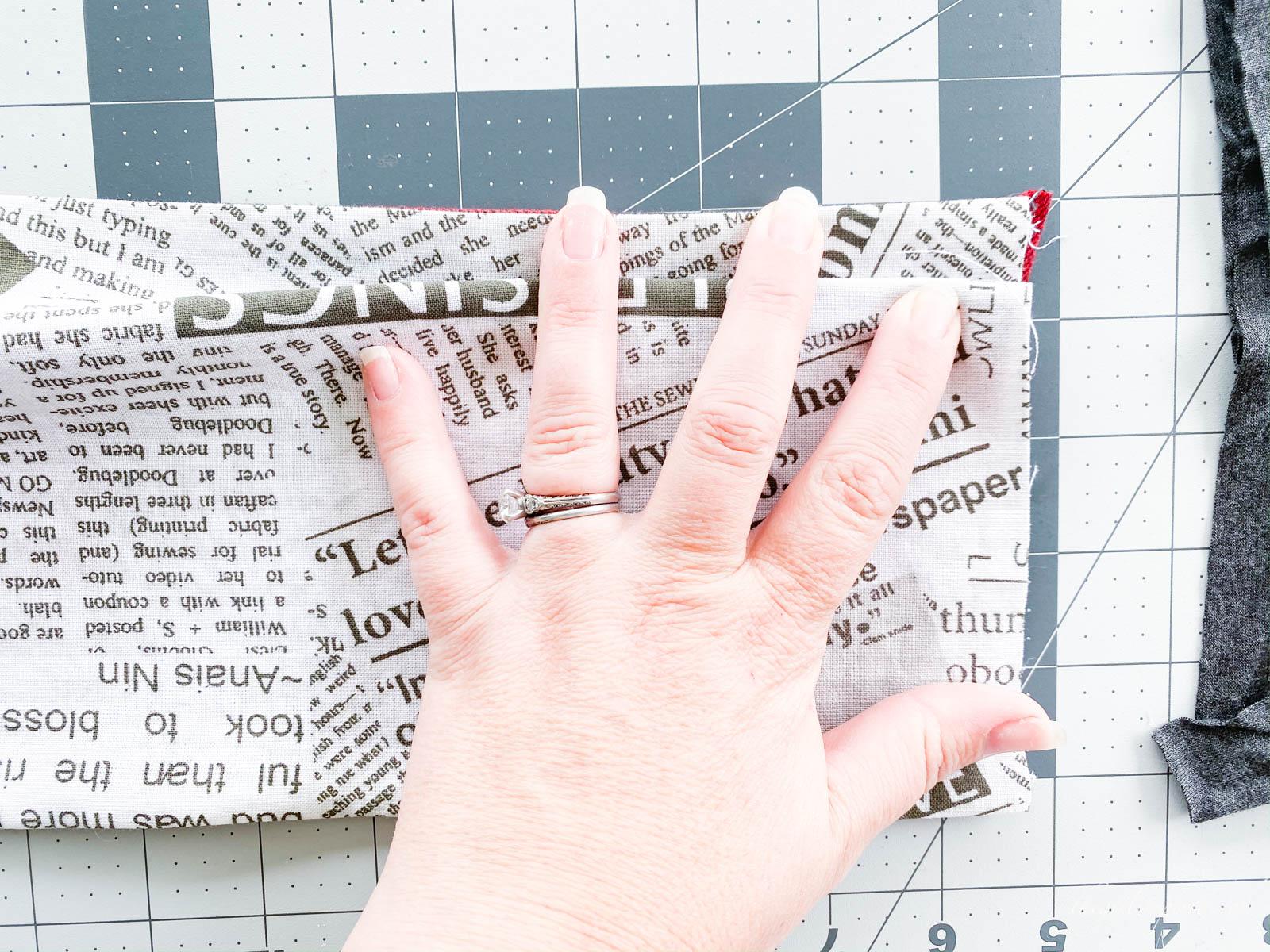 hand folding fabric on rulered mat