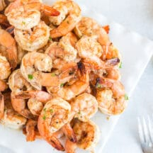 grilled shrimp skewers stacked on white plate with lemon wedges and forks
