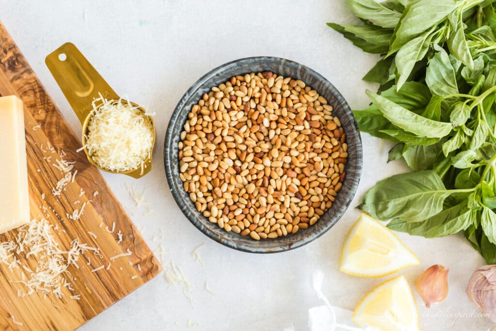 toasted pine nuts in grey pan, parmesan cheese in gold cup, lemon wedges, basil, and cloves of garlic