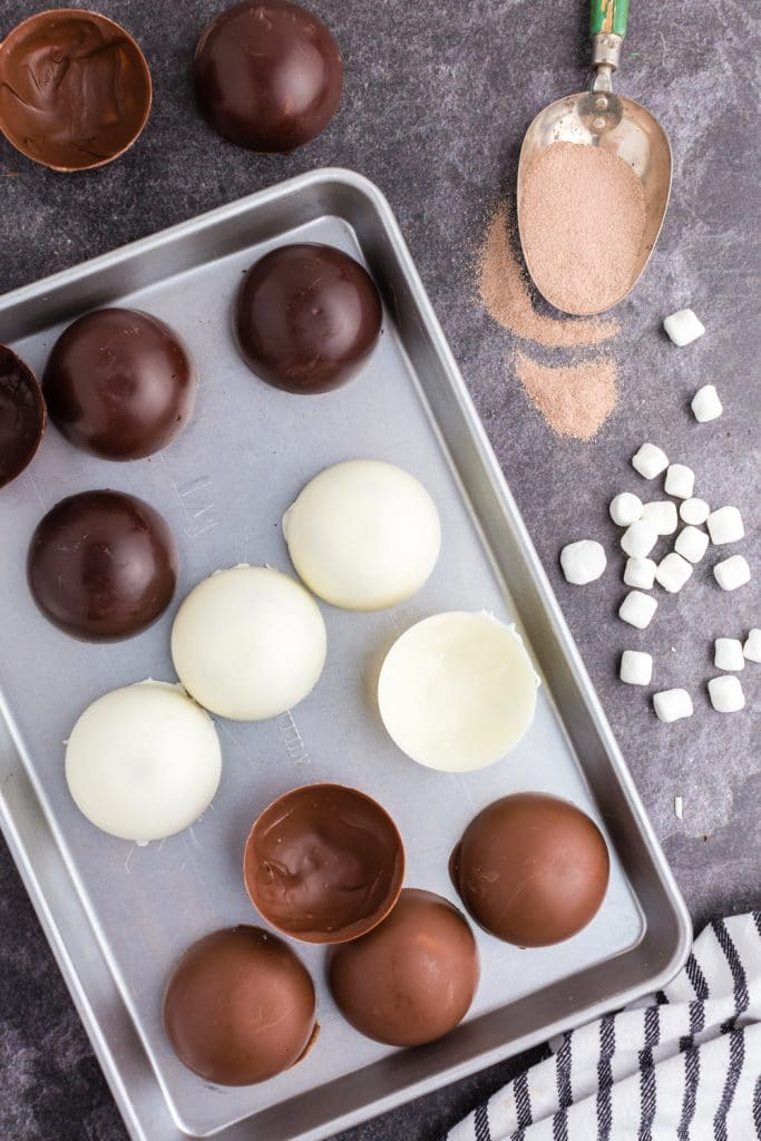 dark, white, and milk chocolate half spheres laid out on baking sheet, cocoa in a scoop, mini marshmallows spread out