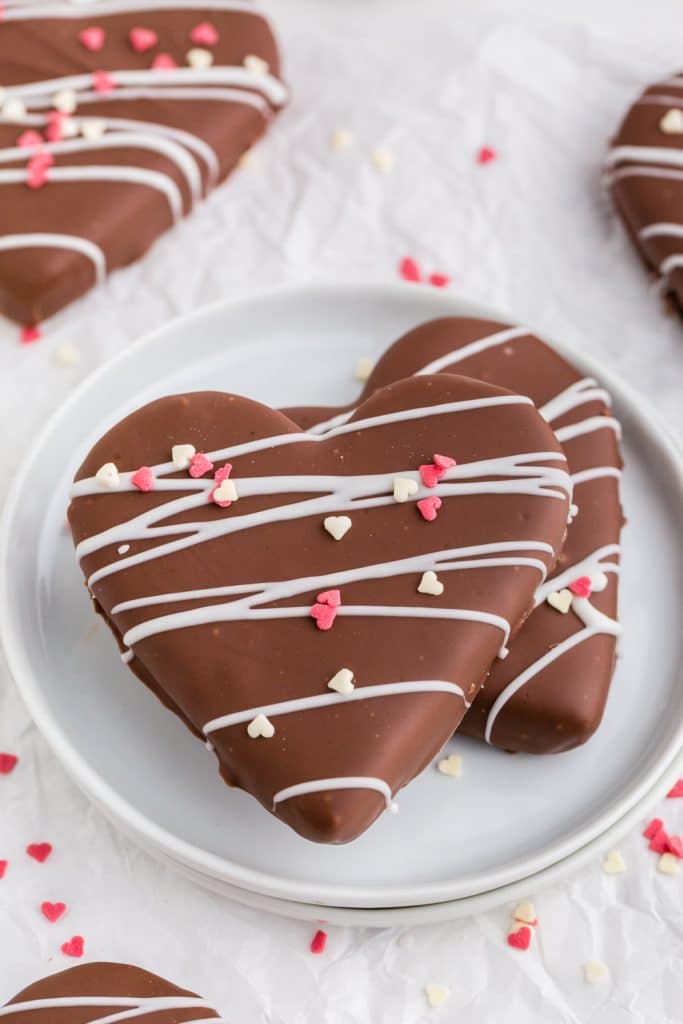 two stacked heart shapes covered in chocolate with white chocolate drizzle and heart sprinkles on white plate