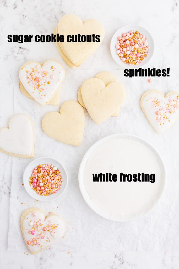 overhead photo of heart shaped Valentine's sugar cookies, some frosted, bowls of pink and gold sprinkles, plate with smooth white frosting, and text overlay