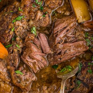 close up of meat falling apart in gravy with potatoes and carrots