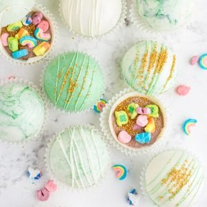 overhead of green and white marbled hot chocolate bombs, some closed, some filled with hot cocoa mix and Lucky Charms