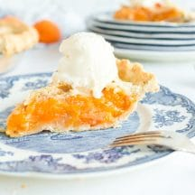 side view of slice of apricot pie with vanilla ice cream on blue plate