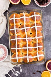 buns in baking dish with icing crosses over the top