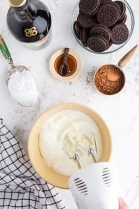 hand mixer beating heavy cream in ceramic bowl with vanilla, powdered sugar, and cocoa powder in bowls nearby