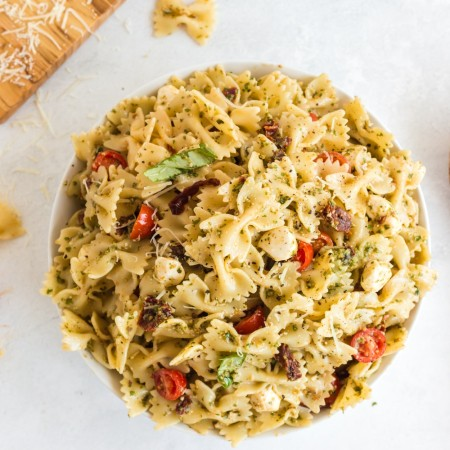 pesto pasta salad in bowl with bread and wooden serving spoon alongside