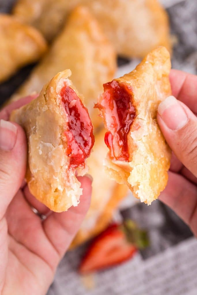 Two hands holding a teared apart Strawberry Rhubarb Hand Pie