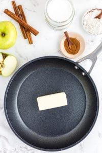 Frying pan with butter, bowl with ground cinnamon, cinnamon sticks, bowl with flour, an apple on marble countertop
