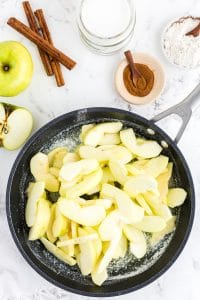 Frying pan with apple slices, bowl with ground cinnamon, cinnamon sticks, bowl with flour, an apple on marble countertop