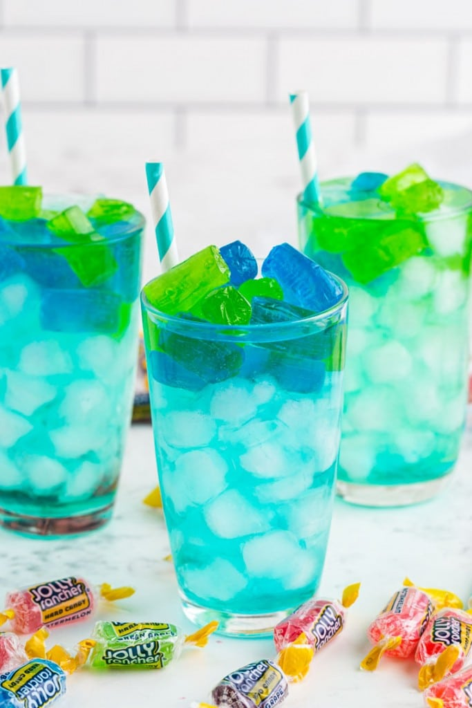 Three glasses of turquoise Jolly Rancher Cocktail with paper straws, jolly rancher candy on marble countertop
