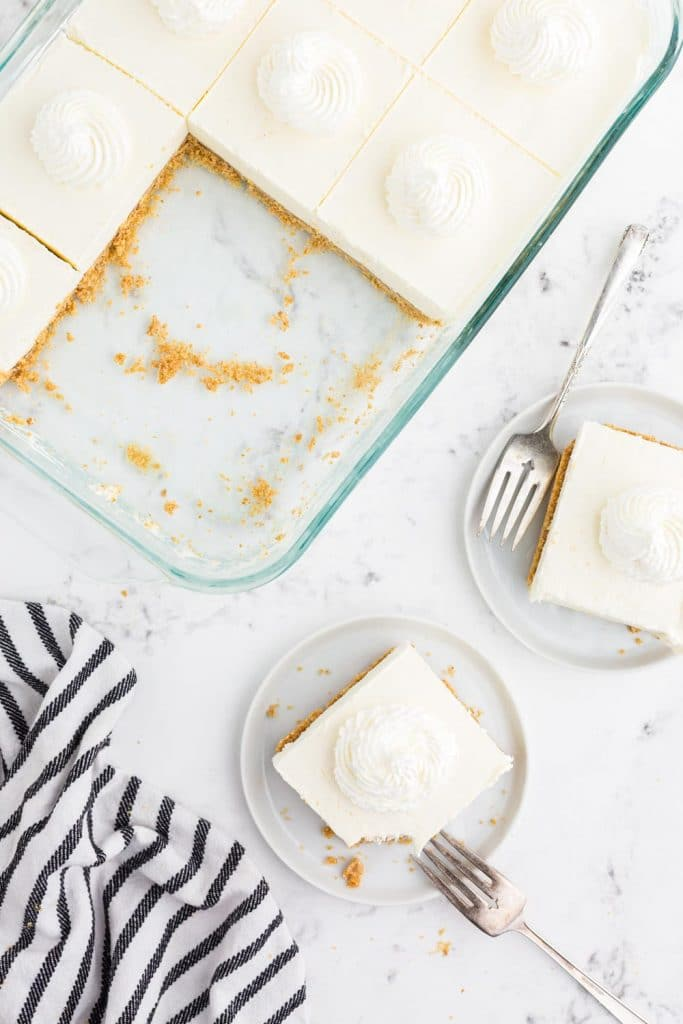 Pie dish with no bake cheese cake with spatula and two missing pieces, two pieces of cake on white cake plates, two forks on a marble countertop