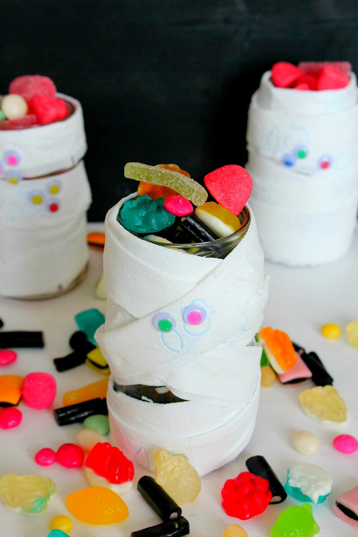Halloween mason jars for treats made with toilet paper and googly eyes
