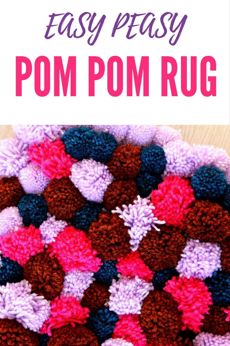 DIY Pom Pom Rug made with yarn pom poms in pink, navy blue, brown and lilac
