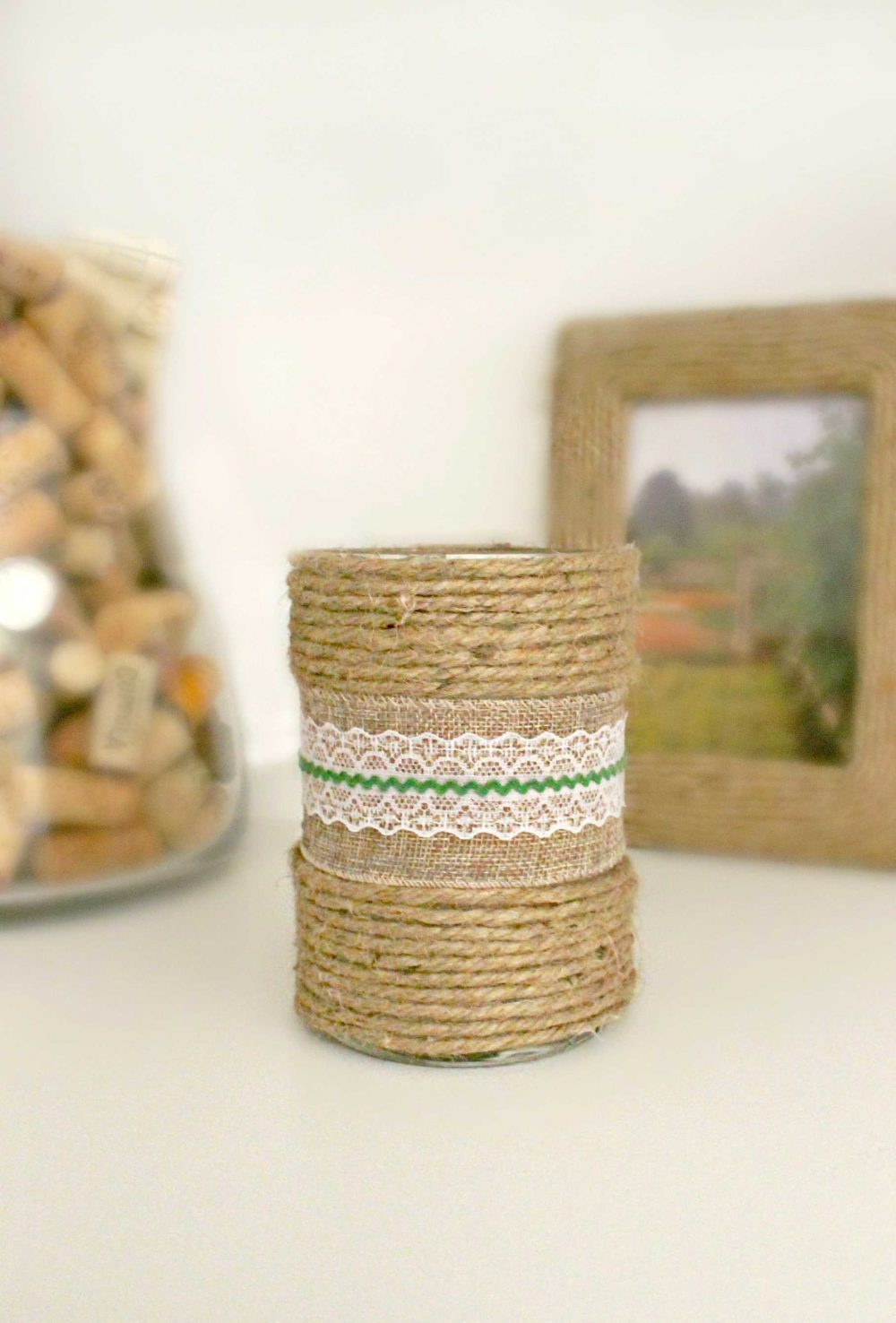 Decorated candles, with burlap ribbon and ric rac in the middle and rows of twine at the bottom and the top