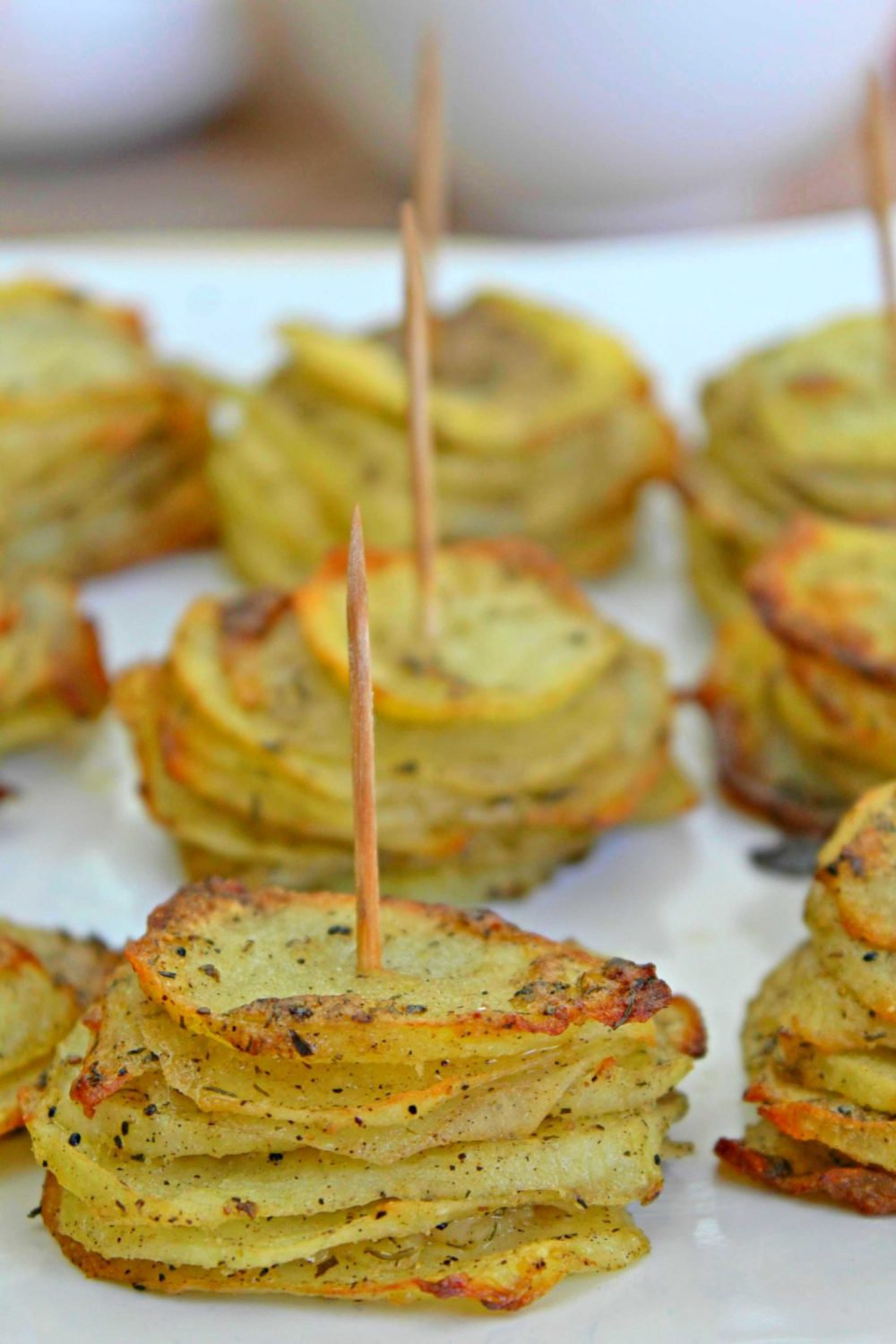 Parmesan potato stacks with garlic and herbs on a white serving plate