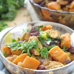 Transparent bowl of Healthy chicken chili with sweet potatoes sprinkled with fresh parsley