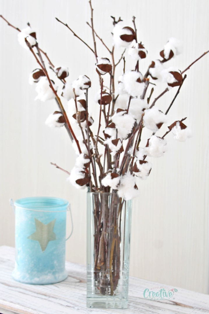 DIY cotton stems with faux cotton branches, in a transparent vase next to a blue candle holder.