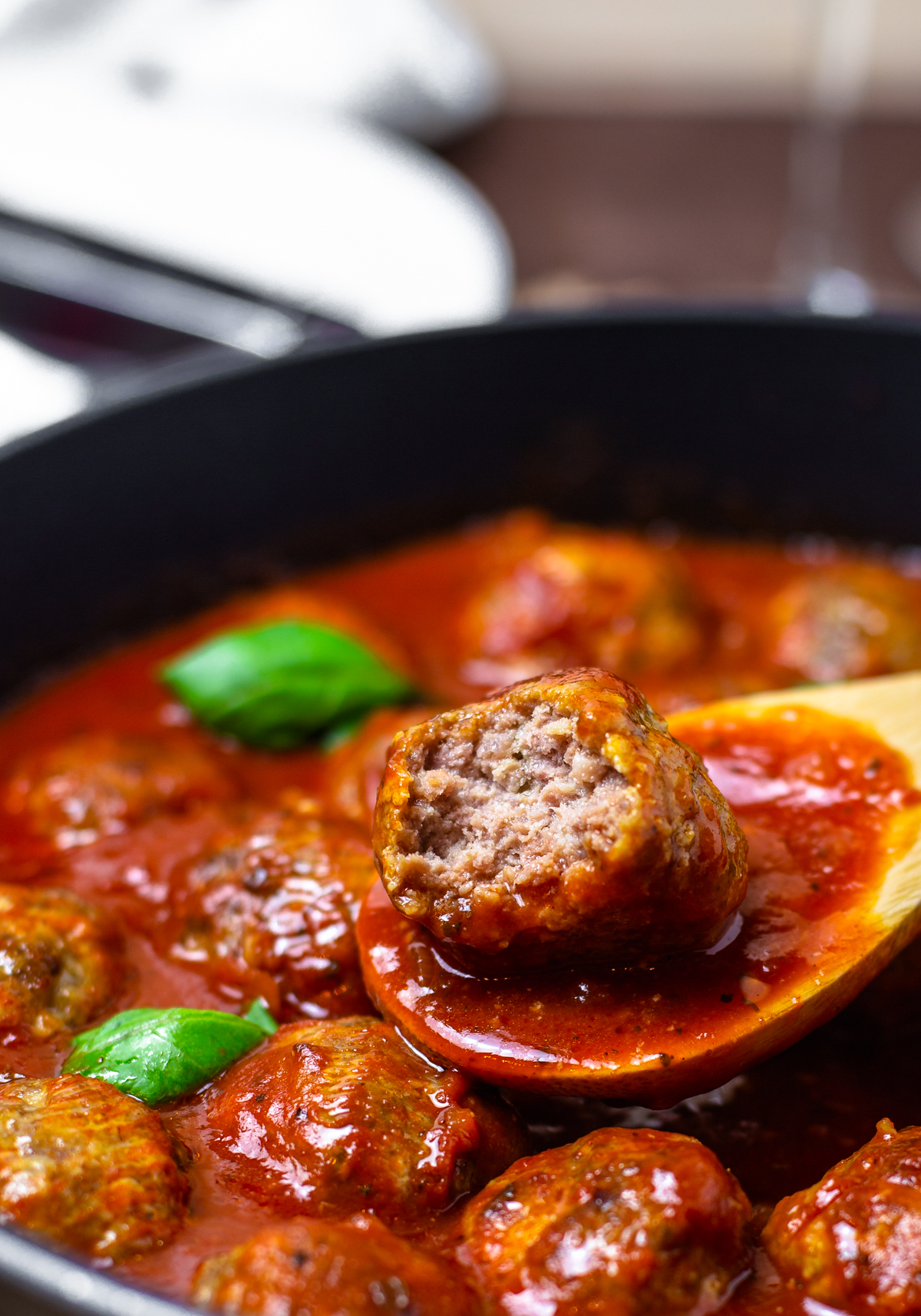 Spoon holding one Homemade Meatball with bite taken out of it