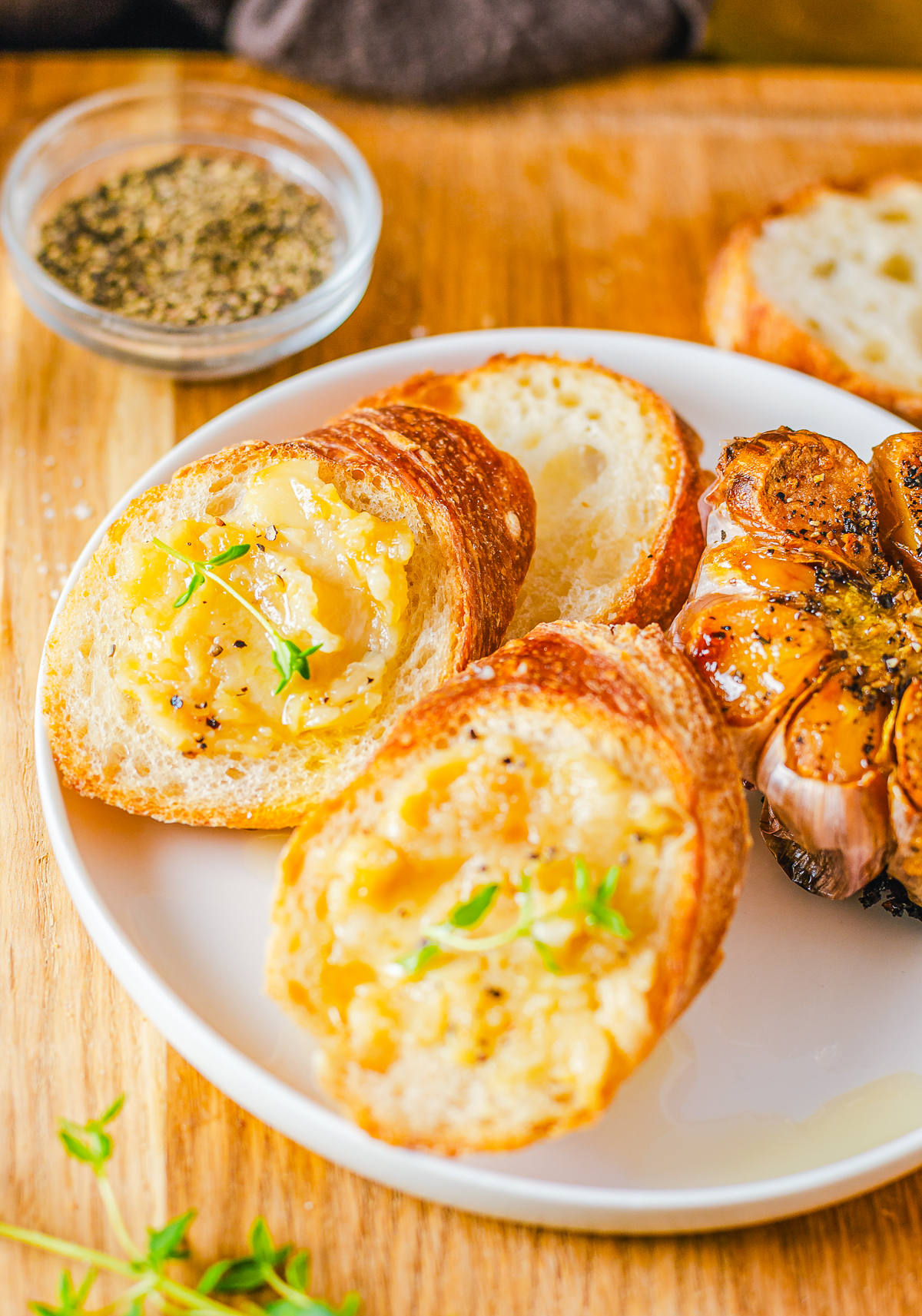 Roast Garlic Spread on slices of bread with a whole garlic on the side.