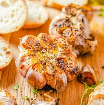 Square image of Roast Garlic with slices of bread on wooden board.