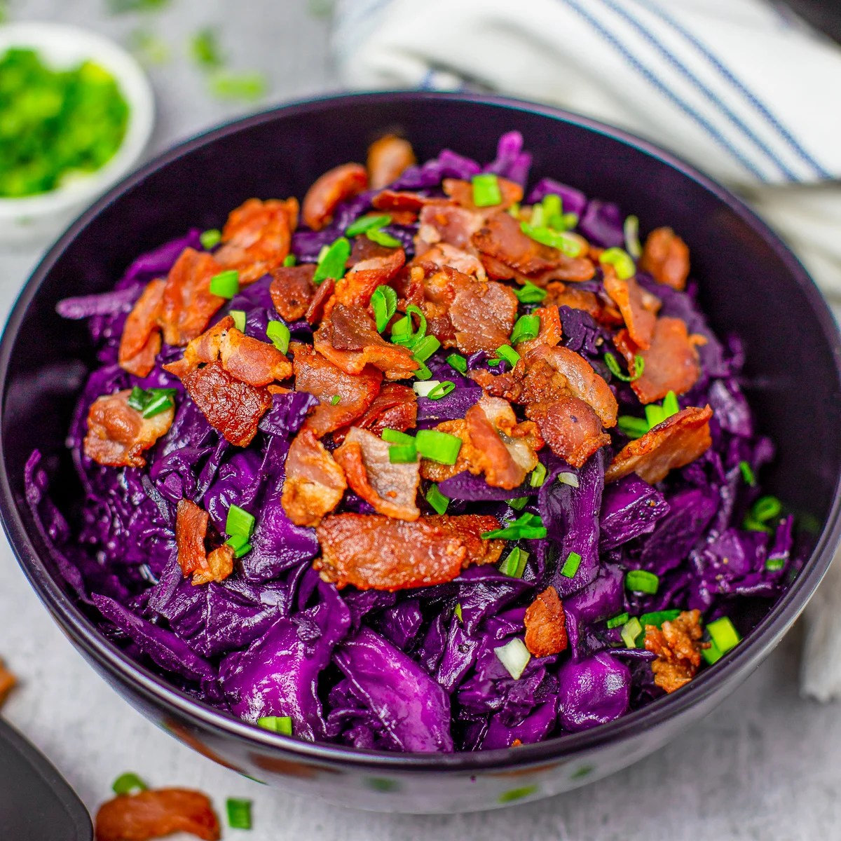 Square image of finished cabbage in bowl with bacon and scallionns.