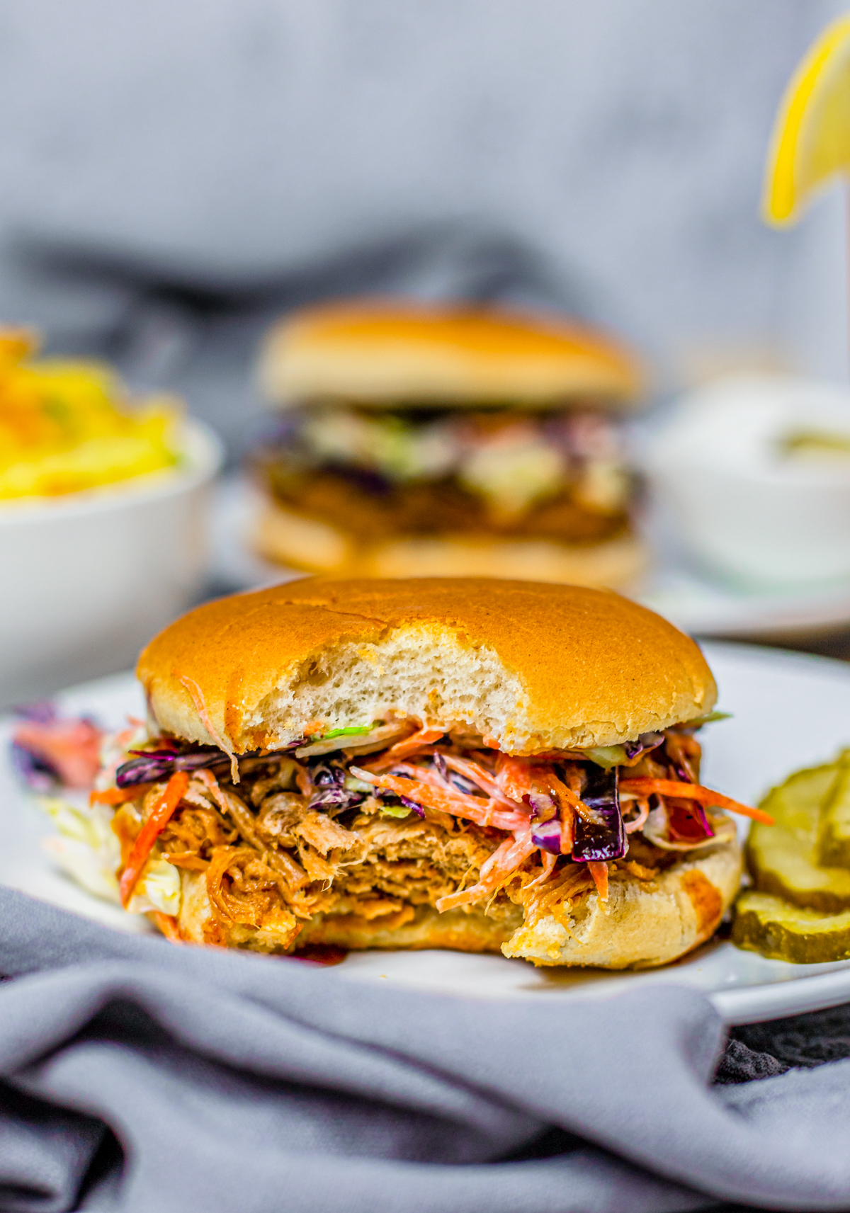 Crock Pot Pulled Pork Sandwich on plate with bite taken out