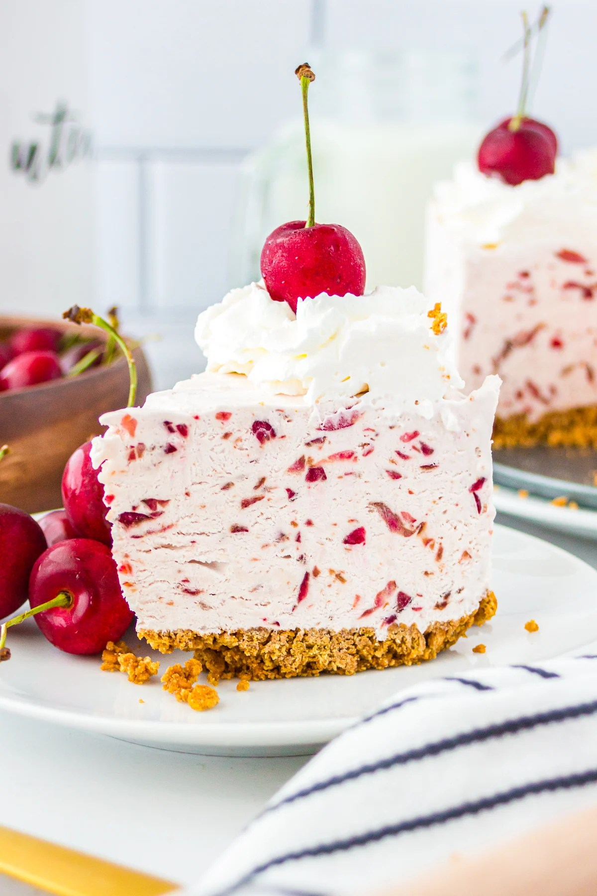 Slice of No Bake Cherry Cheesecake on white plate topped with whipped cream and a cherry
