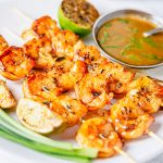 Square image of grilled shrimp on white plate with sauce