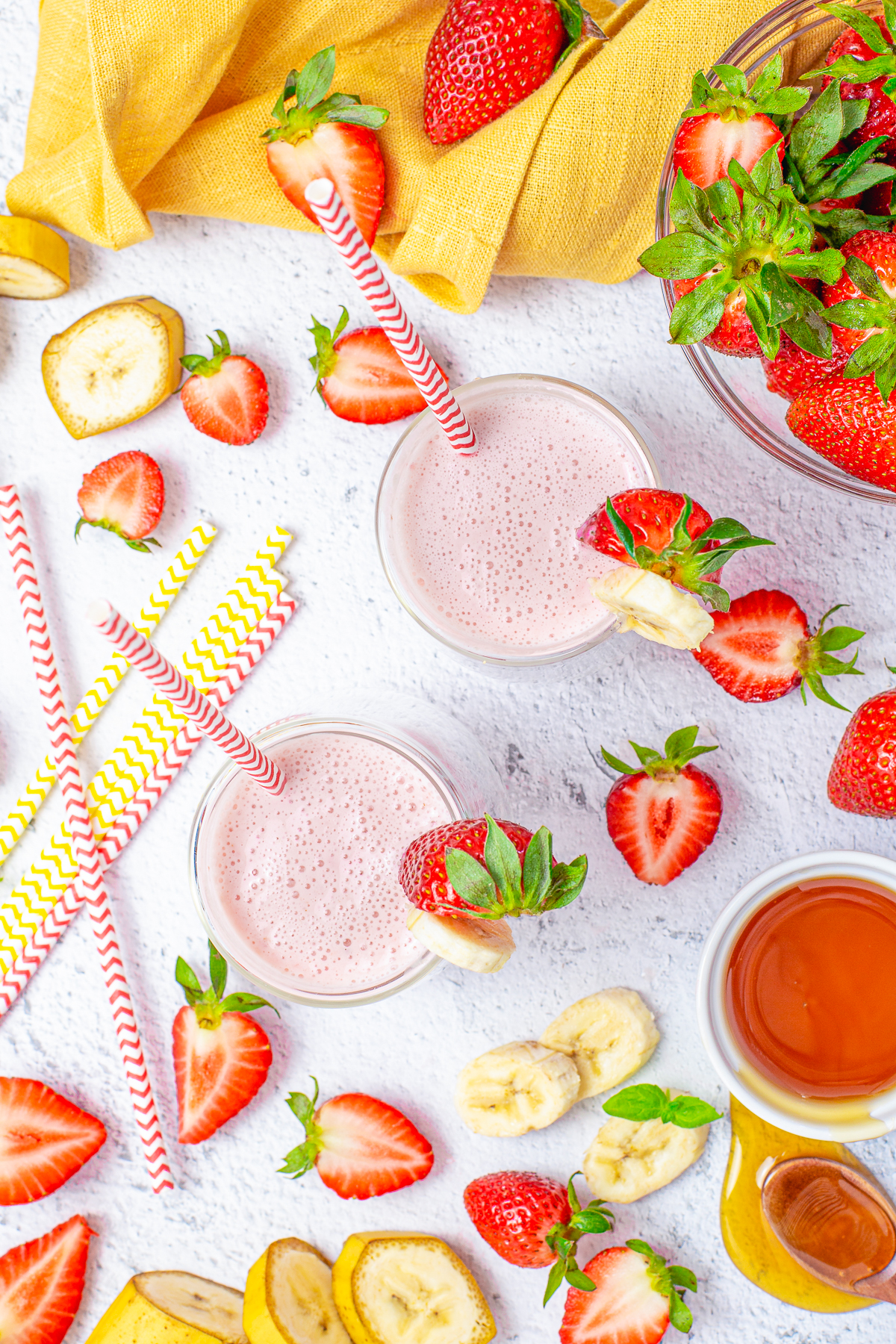 Overhead of two smoothies surrounded by strawberries and bananas