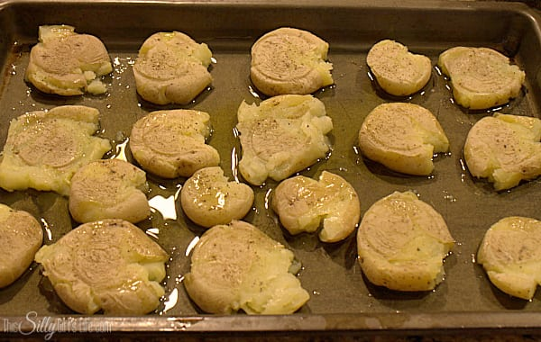 Place potatoes onto sheet tray and with the bottom of a glass, smash them until about 1/2 inch or the thickness of your index finger. Drizzle with the olive oil