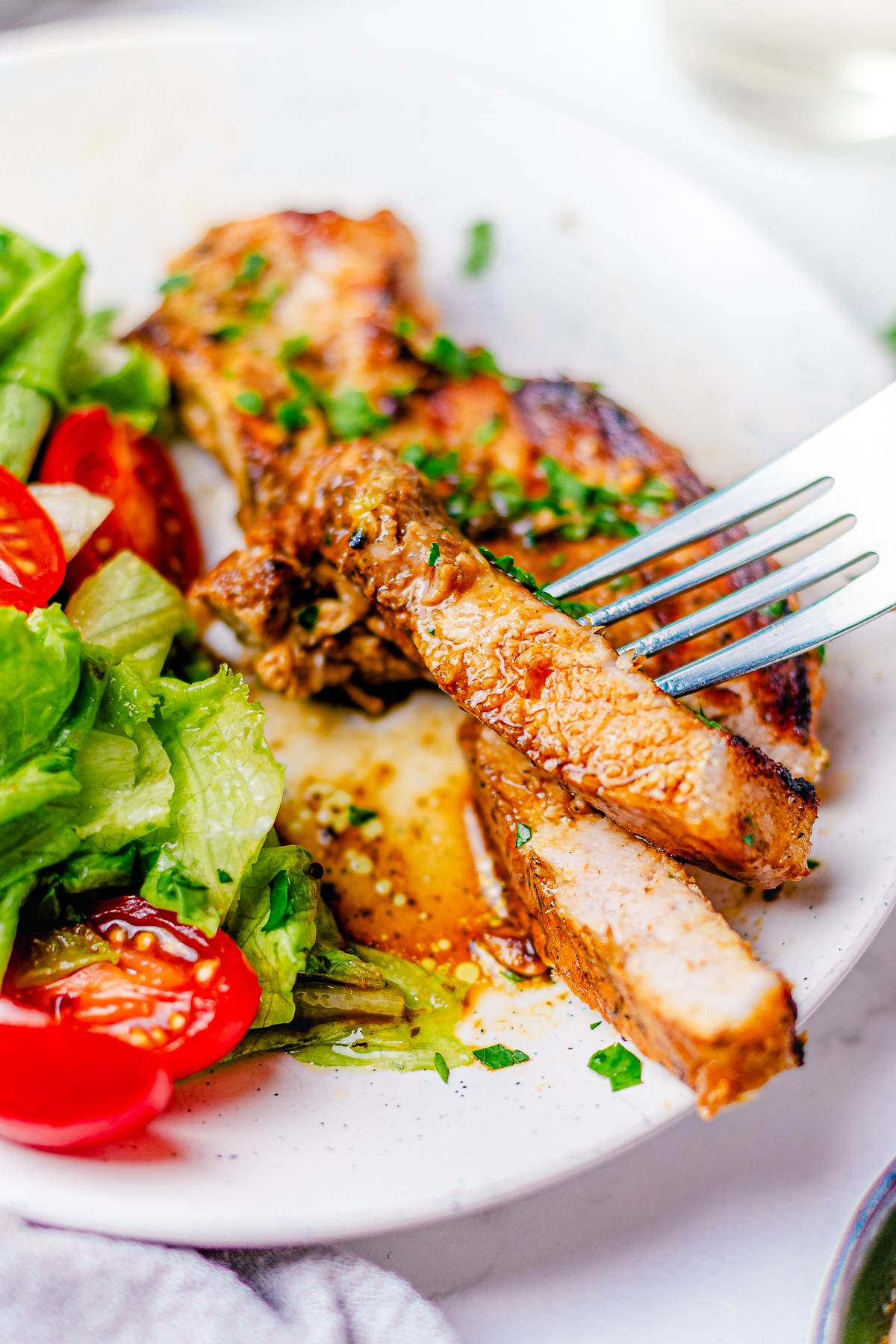 One cut Herb Marinated Grilled Pork Chop Recipe on plate with fork