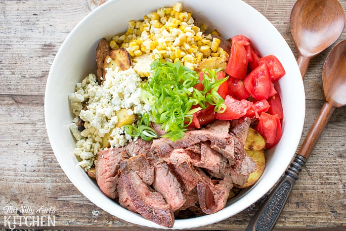 Black and Bleu Potato Salad, blackened flank steak is mixed with grilled potatoes and corn, coated in a luscious bleu cheese dressing! from ThisSillyGirlsLife.com SeeTheLite AD