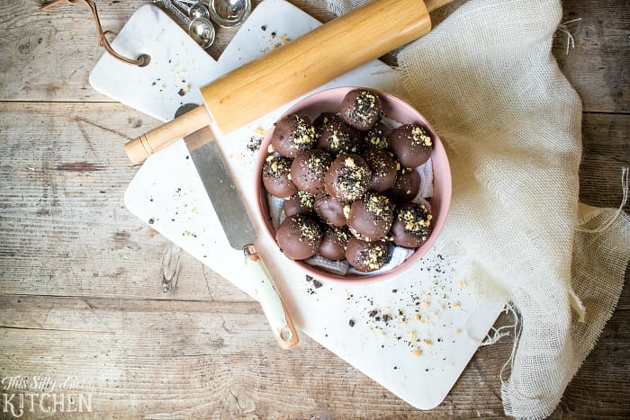 Marble Oreo Truffles overhead on white cutting board with spreader and rolling pin