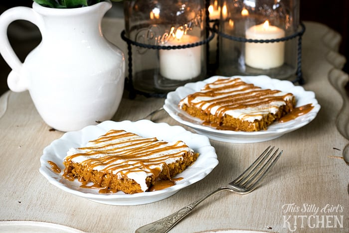 Two slices of cake on white plates with fork and candles in background