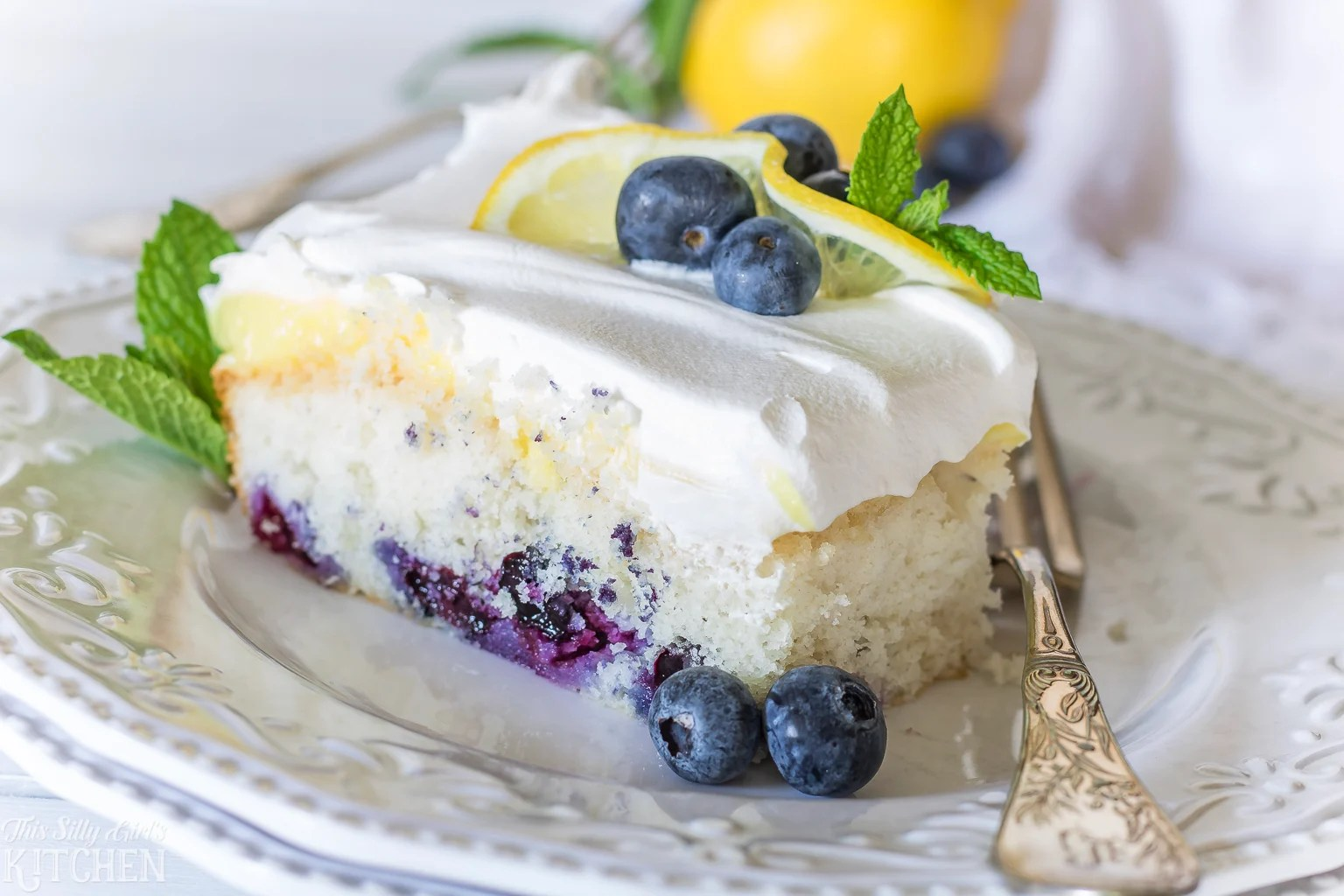 Lemon Blueberry Poke Cake, white cake loaded with fresh blueberries, lemon pudding and whipped topping! Recipe from ThisSillyGirlsKitchen.com