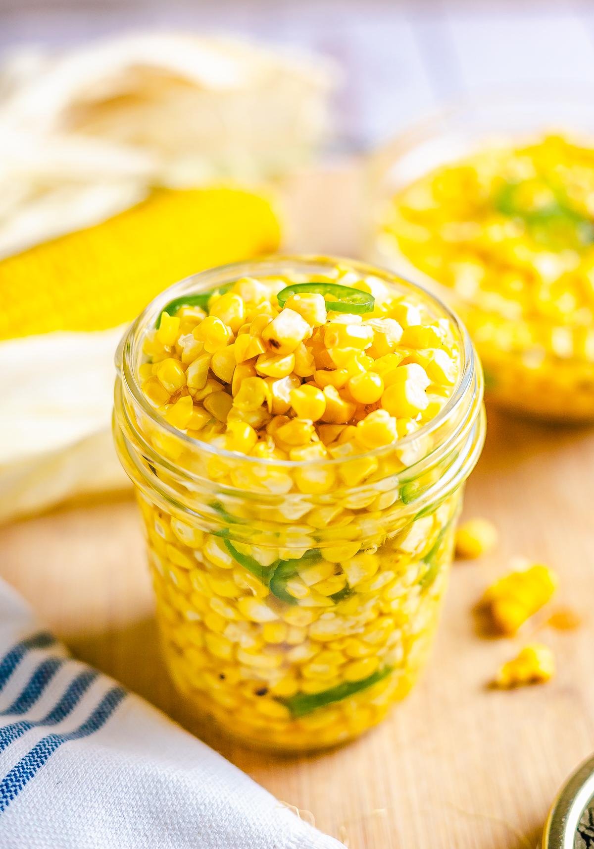 Corn Relish in mason jar with corn in background