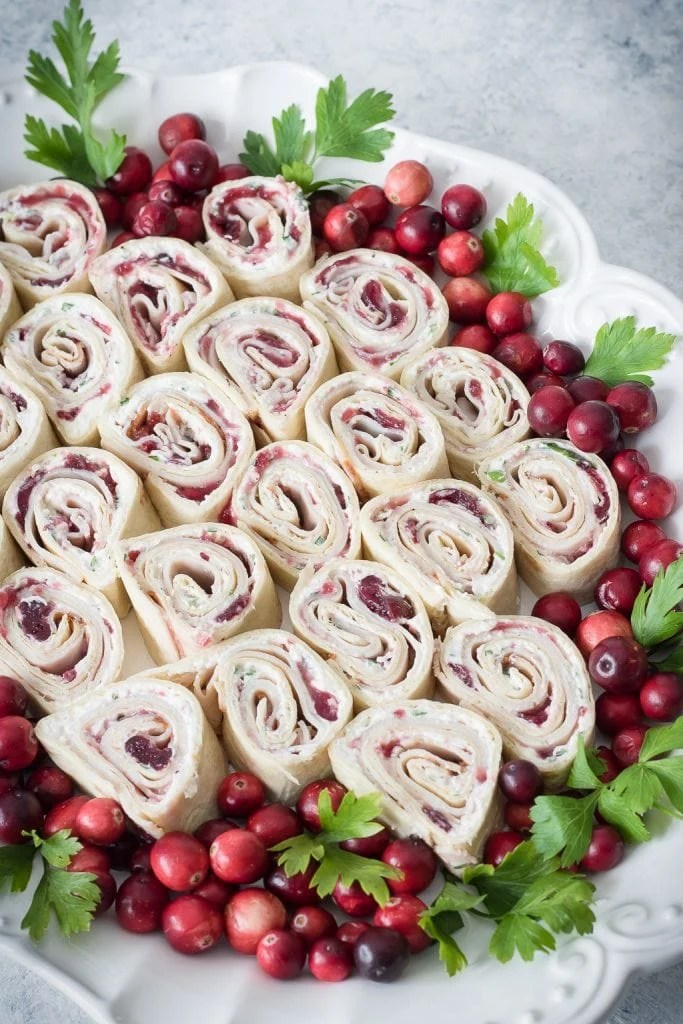 Cranberry Turkey Pinwheels on serving tray with cranberries and parsley