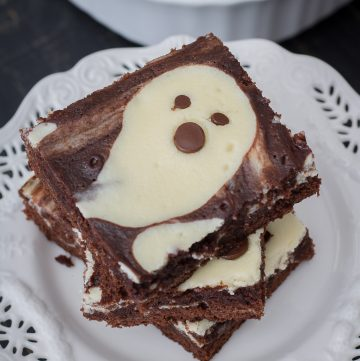 Stacked Ghost Cheesecake Brownies on white plate square image.