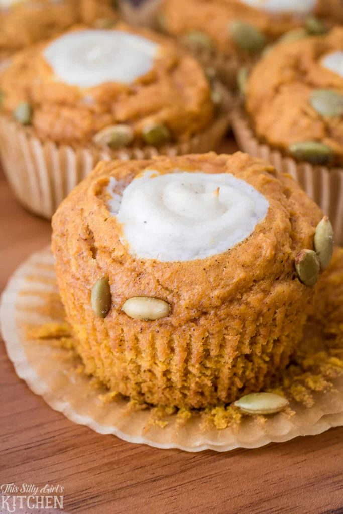 Pumpkin Cream Cheese Muffins, pumpkin muffins stuffed with sweetened cream cheese and garnished with pumpkin seeds. Just like Starbucks, but better! Recipe from ThisSillyGirlsKitchen.com