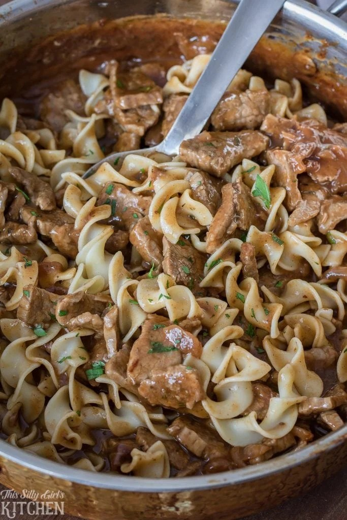 Noodles mixed in with Steakhouse Beef Tips with spoon in pan