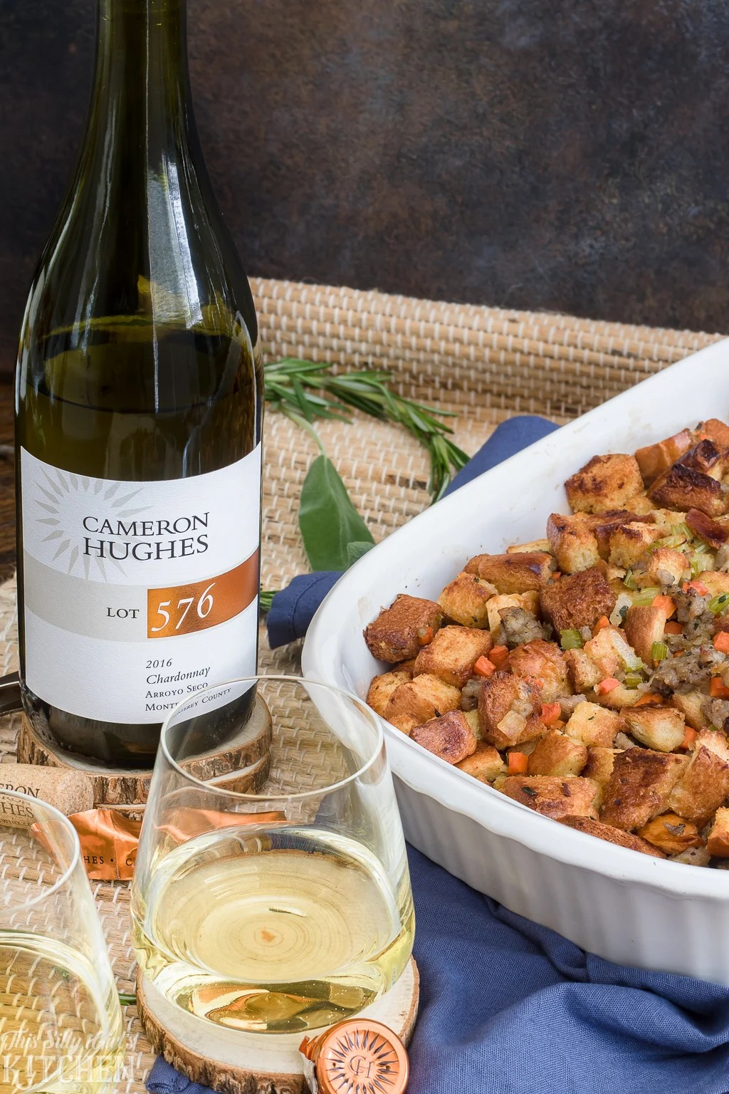 Bottle of wine and glass next to stuffing in casserole dish