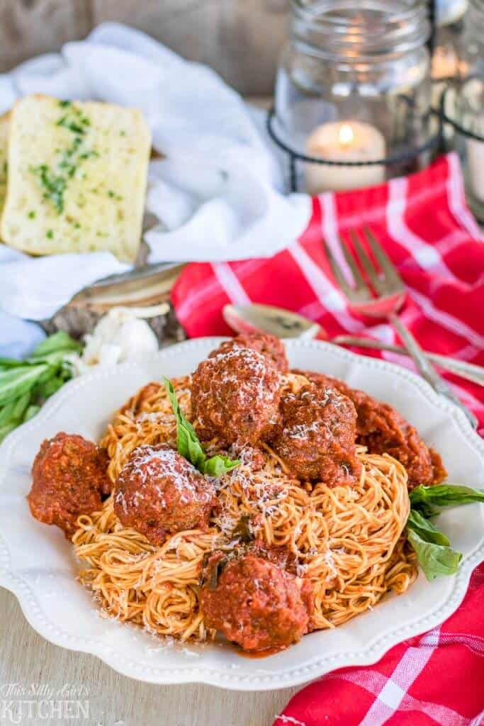 Plated Spaghetti and Meatballs on white plate with basil and garlic bread in background
